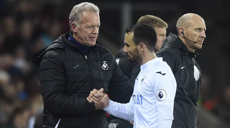 Swansea City caretaker manager Alan Curtis shakes hands with Swansea City's Leon Britton as he is substituted off